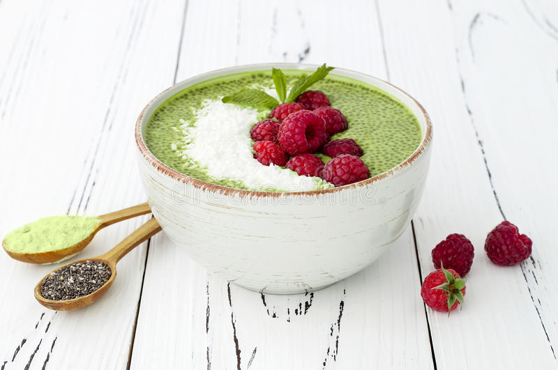 Matcha green tea chia seed pudding bowl, vegan dessert with raspberry and coconut milk. Overhead, top view, flat lay. Matcha green tea chia seed pudding bowl stock images