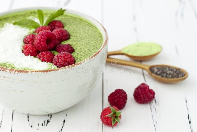 Matcha green tea chia seed pudding bowl, vegan dessert with raspberry and coconut milk. Overhead, top view, flat lay. Matcha green tea chia seed pudding bowl stock photo