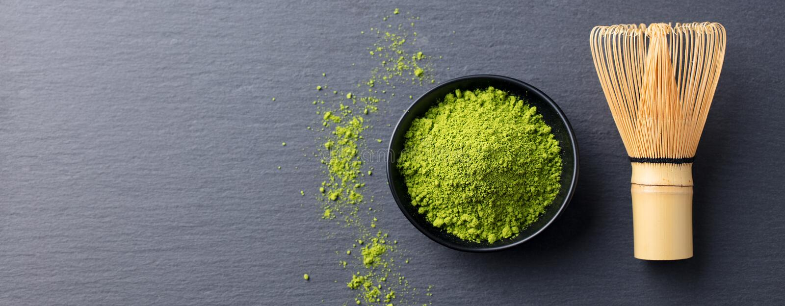 Matcha green tea cooking process in a bowl with bamboo whisk. Black slate background. Copy space. Top view. royalty free stock images