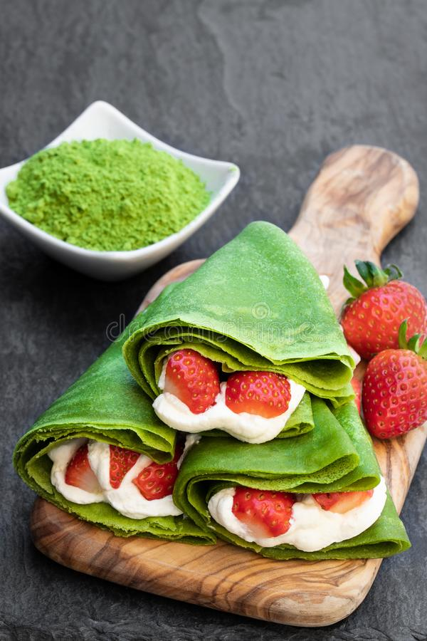 Matcha green tea crepe with whipped cream and strawberry on serving board. Matcha  green tea crepe with whipped cream and strawberry on serving board royalty free stock image