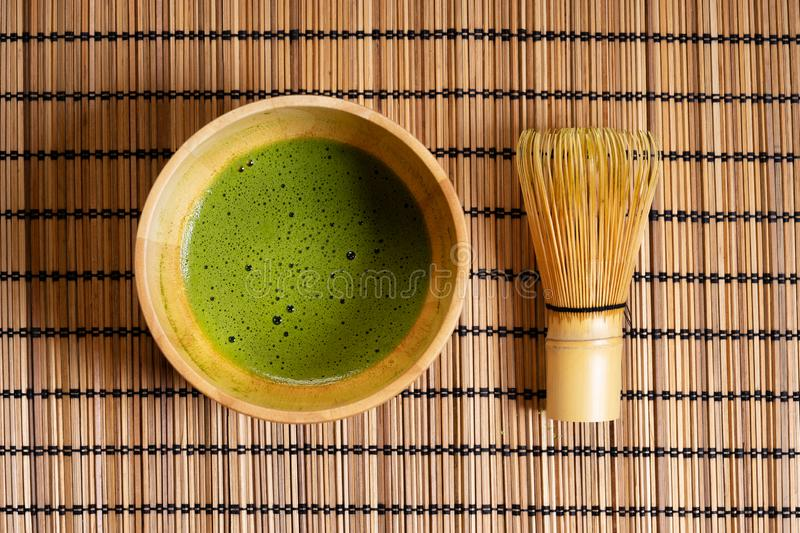 Matcha green tea drink in wooden bowl with bamboo whisk royalty free stock photos