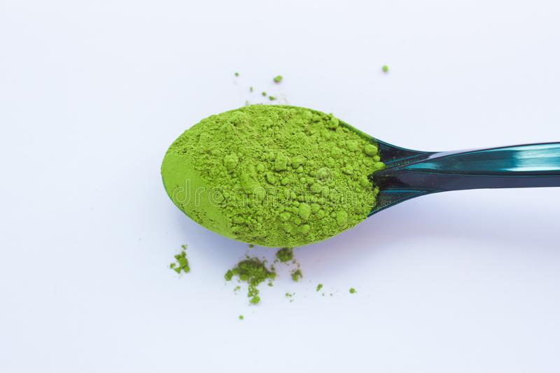 A spoon with powdered matcha green tea, isolated on light background, copy space, top view. Matcha green tea on light background. A spoon with traditional stock photography