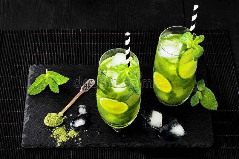 Matcha iced green tea with lime and fresh mint on black stone slate background. Super food drink. royalty free stock image