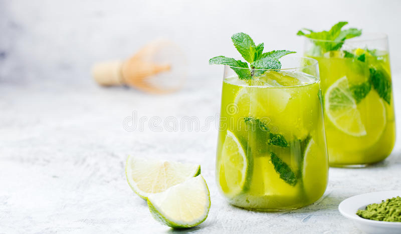 Matcha iced green tea with lime and fresh mint on a marble background. Copy space stock image