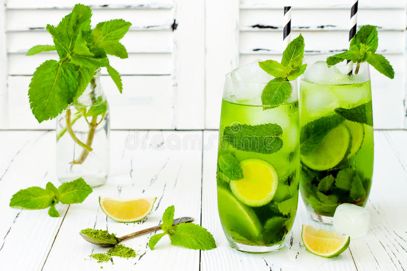 Matcha iced green tea with lime and fresh mint on white rustic background. Super food drink. Matcha iced green tea with lime and fresh mint on white rustic stock images