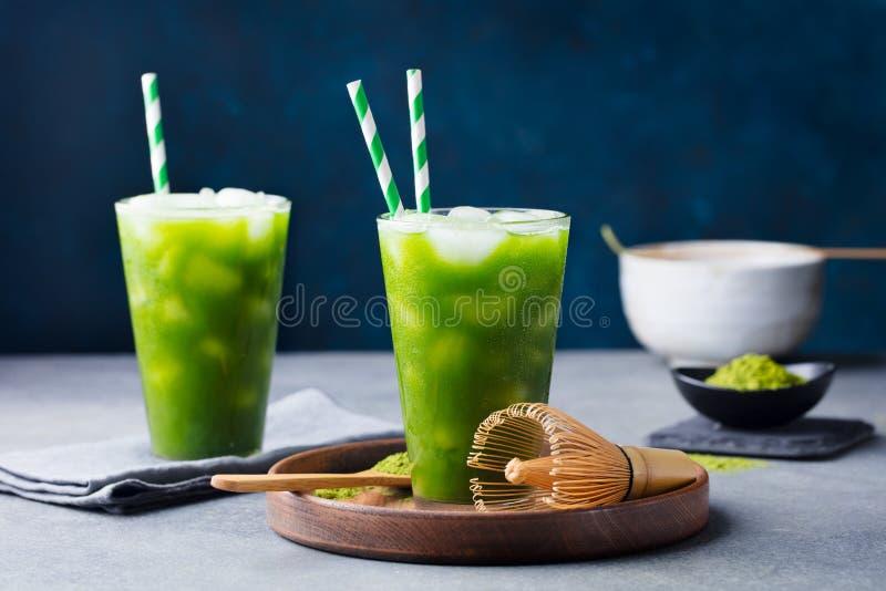 Matcha iste för grönt te, coctail i högväxt exponeringsglas på träplattan gr? sten f?r bakgrund arkivfoto