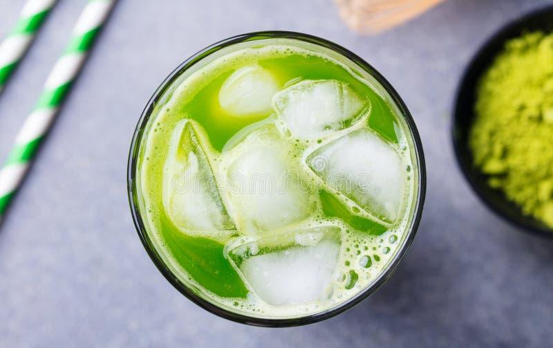Matcha iste för grönt te i högväxt exponeringsglas grå sten för bakgrund close upp arkivfoto