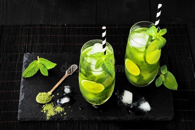 Matcha kritiserar med is grönt te med limefrukt och den nya mintkaramellen på den svarta stenen bakgrund Toppen matdrink royaltyfri bild