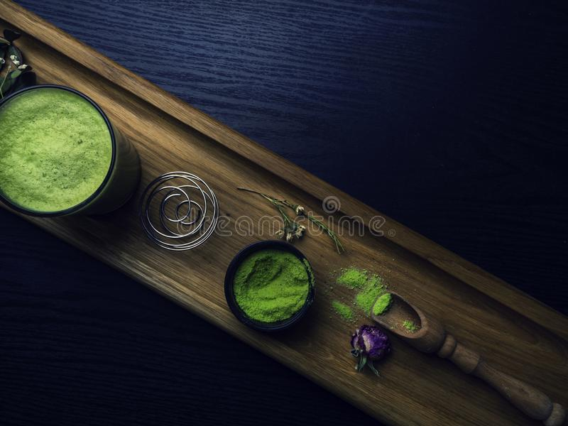 Matcha latte, matcha green tea powder, flowers, wooden spoon and whisk on blue wooden background. Copy space, top view royalty free stock photos