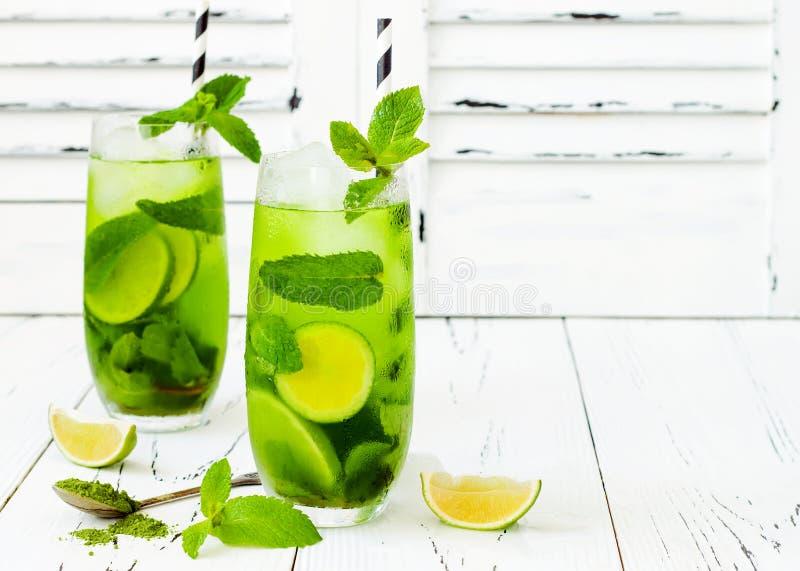 Matcha med is grönt te med limefrukt och den nya mintkaramellen på vit lantlig bakgrund Toppen matdrink royaltyfri foto