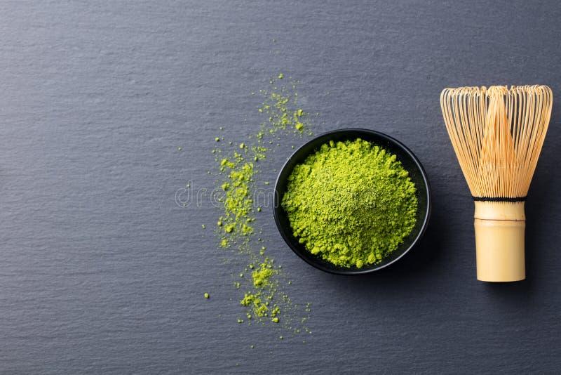 Matcha, pó do chá verde na bacia preta com o batedor de ovos de bambu no fundo da ardósia Vista superior Copie o espaço fotos de stock royalty free