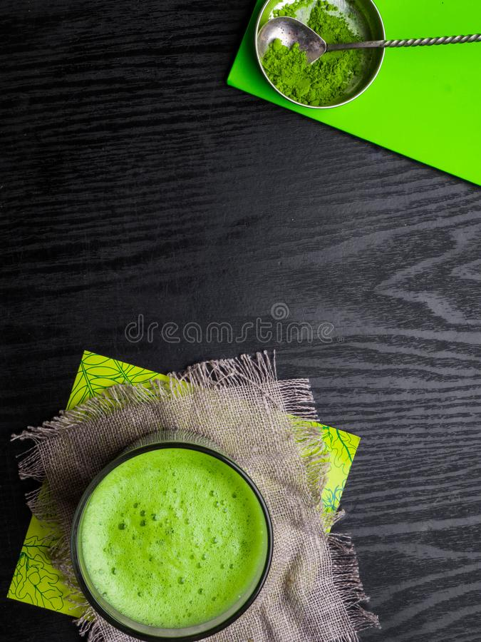 Matcha powder explosion and Matcha latte in glass made from finely ground green tea powder. It\'s very common in japanese culture. stock images