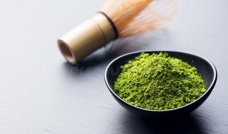 Matcha, Pulver des grünen Tees in der schwarzen Schüssel mit Bambus wischen auf Schieferhintergrund Kopieren Sie Platz stockbild