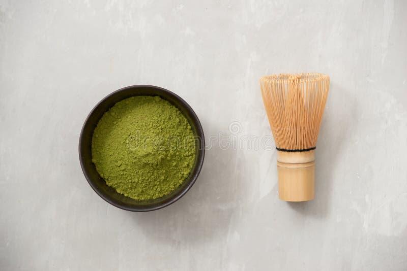Matcha, Pulver des gr?nen Tees in der schwarzen Sch?ssel mit Bambus wischen auf Schieferhintergrund Beschneidungspfad eingeschlos stockfoto