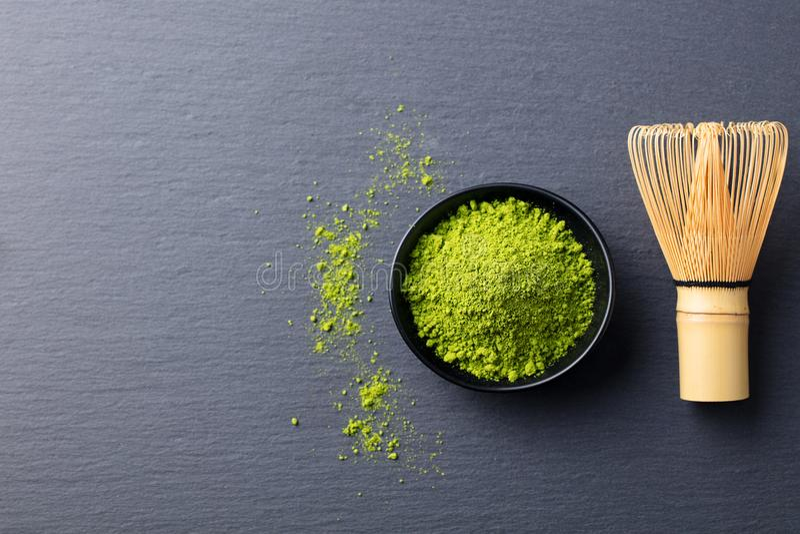 Matcha pulver för grönt te i svart bunke med bambu viftar kritiserar på bakgrund Top beskådar kopiera avstånd royaltyfria foton