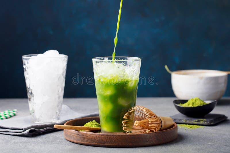 Matcha, tè di ghiaccio del tè verde che versa in vetro alto sul piatto di legno Fondo blu grigio immagine stock libera da diritti
