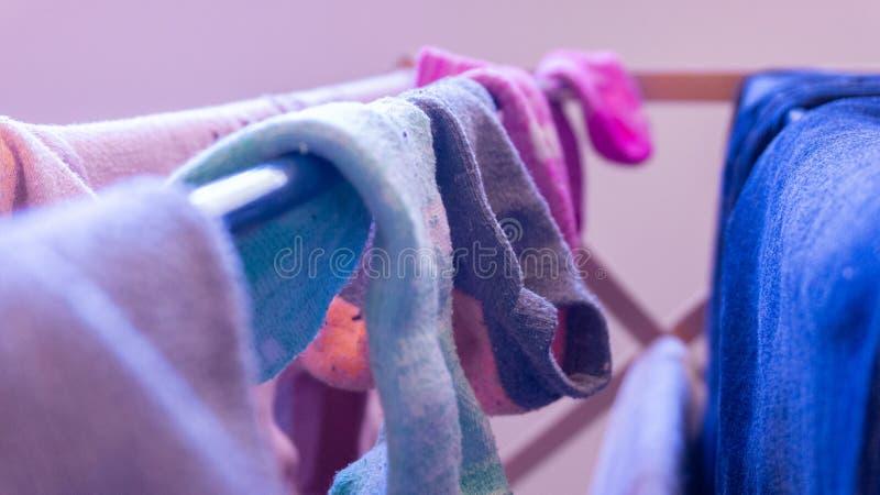 Matchade dåligt sockor som torkar på en kugge, dag Visa tvätteridagen, lokalvård, hussysslor och miss av sockapar arkivbild