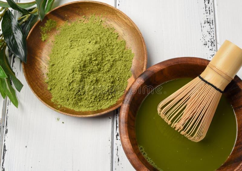 Matchapulver för grönt te i en träbunke med en vifta royaltyfri foto