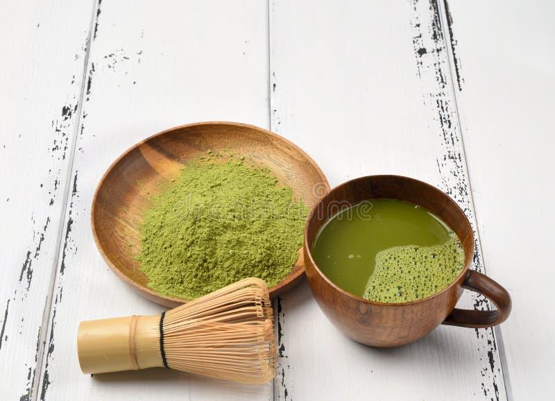 Matchapulver för grönt te i en träbunke med en vifta royaltyfria foton