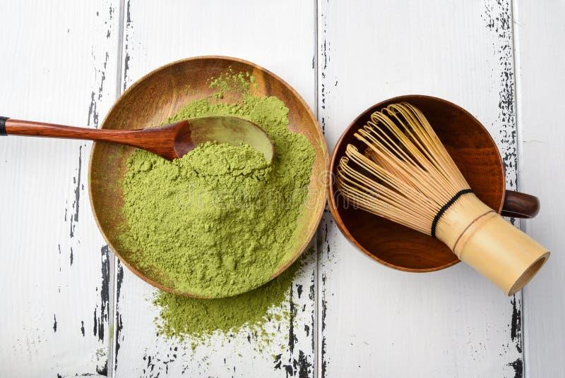 Matchapulver för grönt te i en träbunke med en vifta arkivfoto