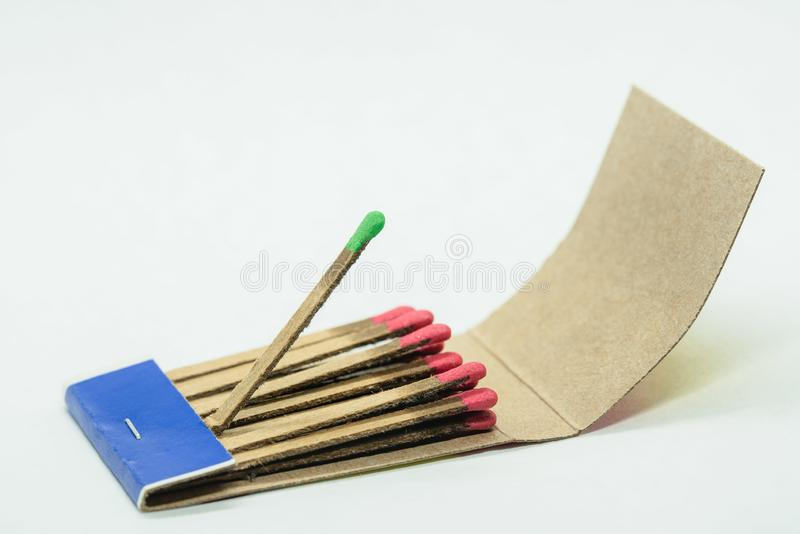 Matchbox isolated on white background. Isolated paper matchbox with all matches having red head while one sticking out match has a green one. Conceptual image stock photo
