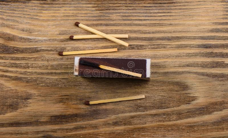 Matches with gray and burnt match on the verge of a matchbox stock image