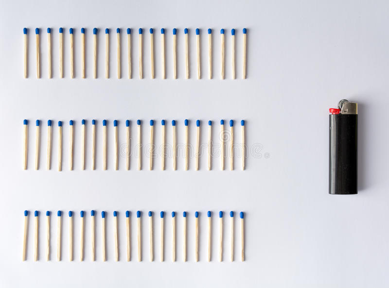 Matches and a lighter in front of a white background. Various matches and a lighter in front of a white background, abstract, symbolizing progress stock photography