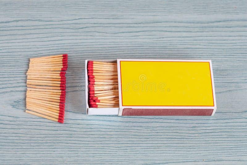 Matchstick fuera de la caja de cerillas en la madera del color foto de archivo