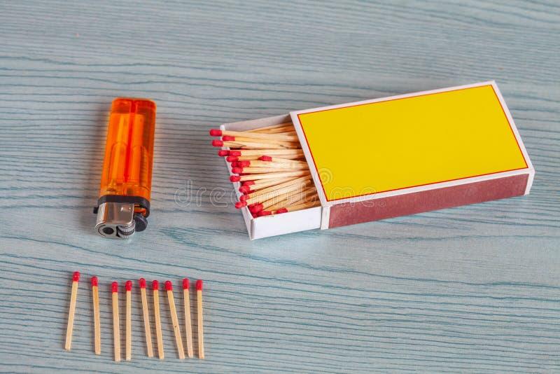 Matchstick y encendedores en la madera del color fotos de archivo libres de regalías