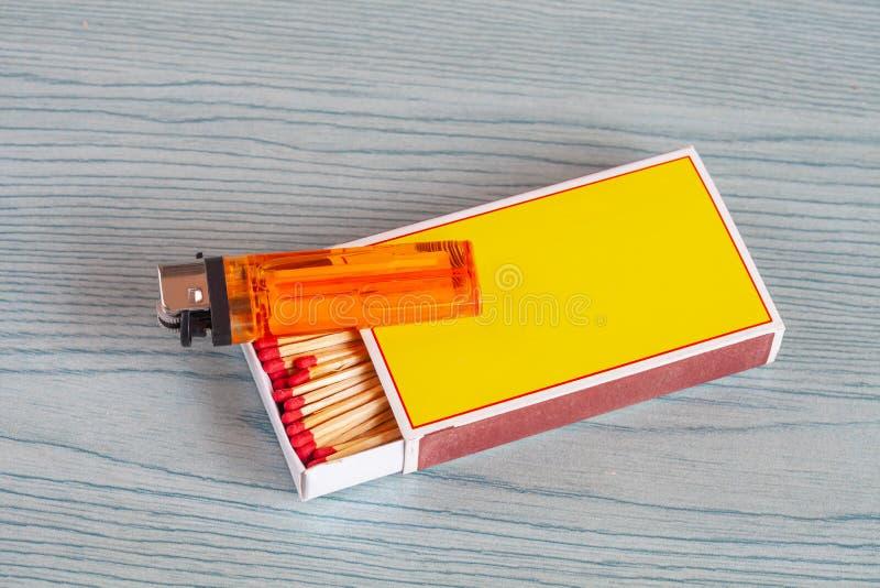 Matchstick y encendedores en la tabla de color imagen de archivo