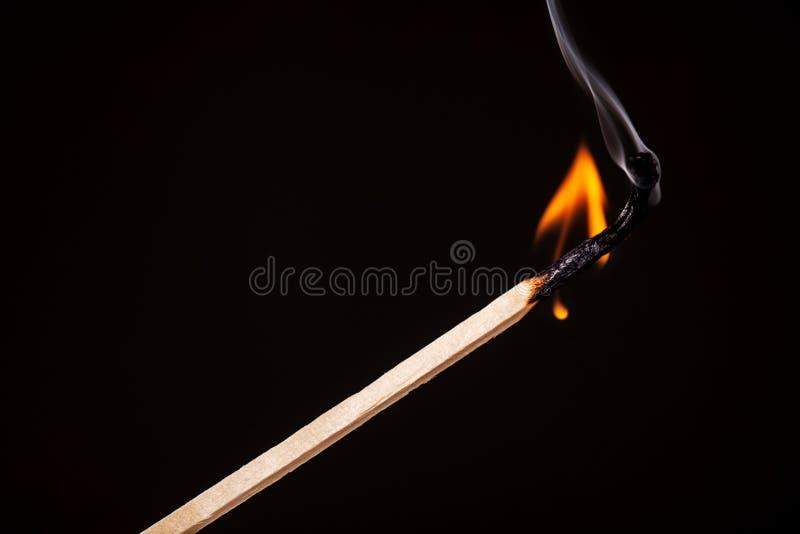 Matchstickbränning mot svart royaltyfri foto