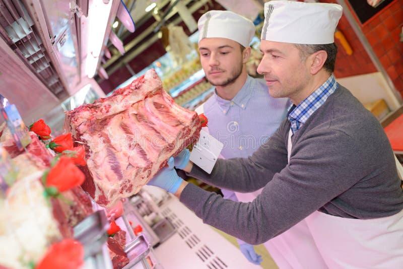 Mate los jóvenes de enseñanza uno cómo vender la carne fotos de archivo