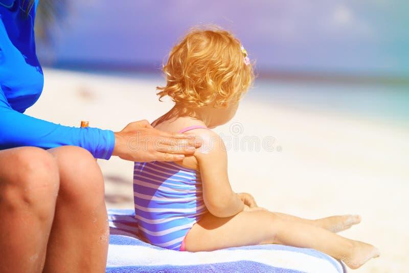 Mateczna stosuje sunblock śmietanka na dziecka ramieniu obrazy royalty free