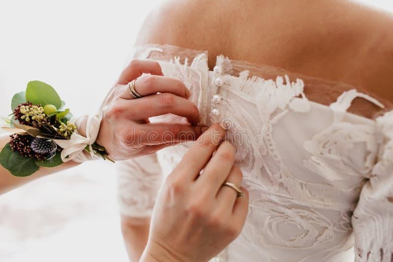 Matek pomoce przymocowywają ślubną suknię przed ceremonią panna młoda pojęcia sukni panny młodej portret schodów poślubić grafika zdjęcia royalty free