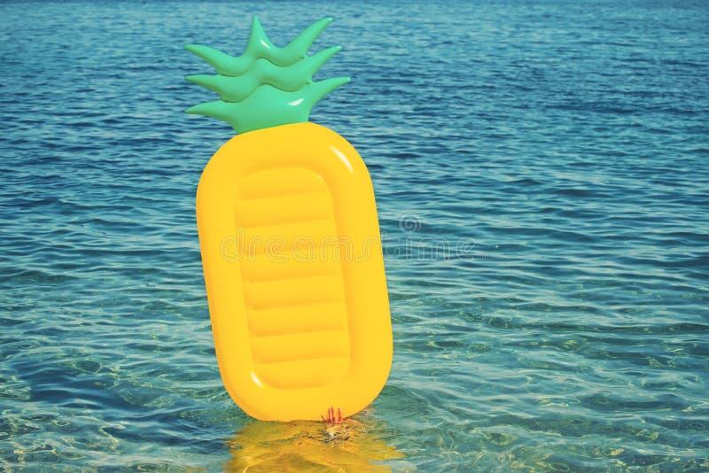 Matelas gonflable d'ananas sur le fond d'eau de mer Vacances et voyage d'été vers l'océan activité et joie sur la plage photos stock