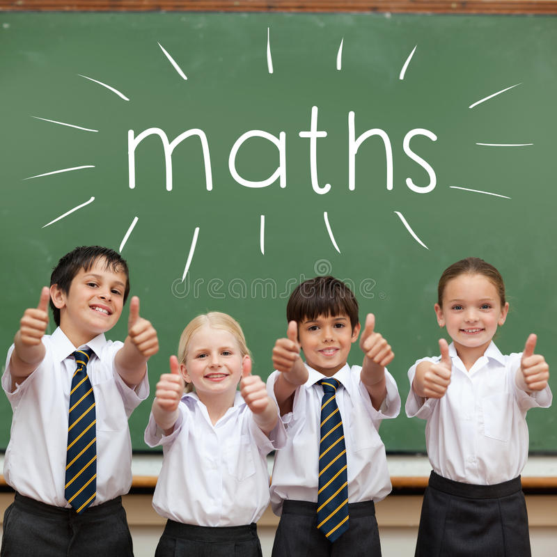 Matemáticas contra os alunos bonitos que mostram os polegares acima na sala de aula imagens de stock royalty free