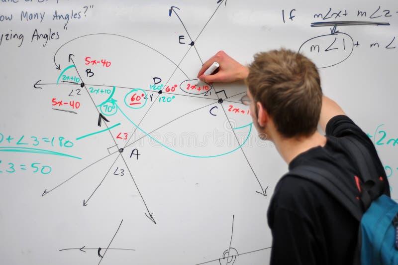 Matemáticas de la escritura del estudiante en whiteboard imagenes de archivo