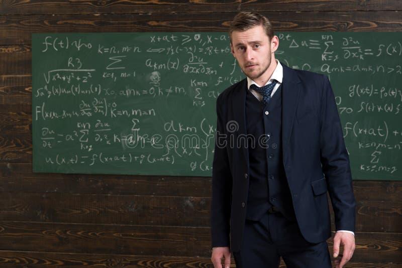 Matemático talentoso El traje clásico del desgaste formal del hombre parece elegante, pizarra con el fondo de las ecuaciones Geni foto de archivo