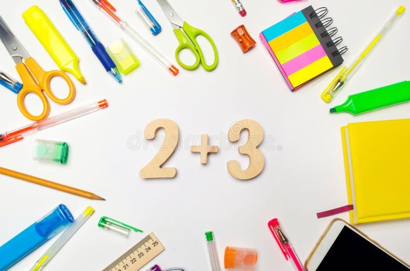 matematica numeri 2 più 3 sullo scrittorio della scuola Concetto di formazione Di nuovo al banco cancelleria Priorità bassa bianc fotografia stock
