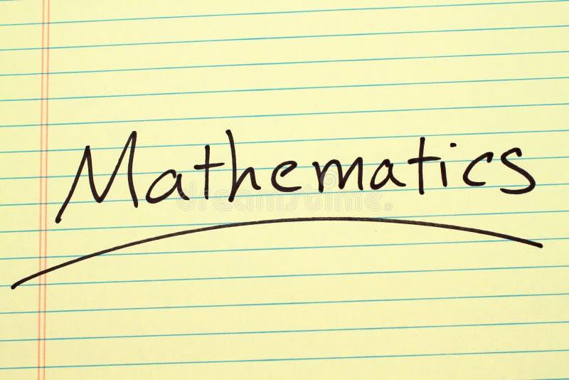 Matematica su un blocco note giallo fotografie stock