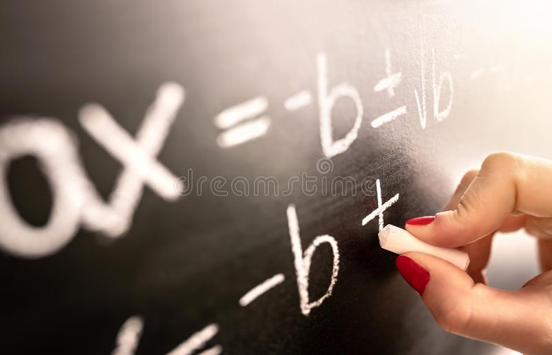 Matematiklärare som skriver funktion, likställande eller beräkning på svart tavla i skolaklassrum fotografering för bildbyråer