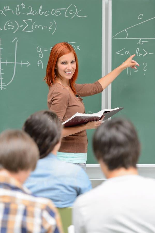 Matematikstudentflicka som pekar på den svart tavlan arkivbilder