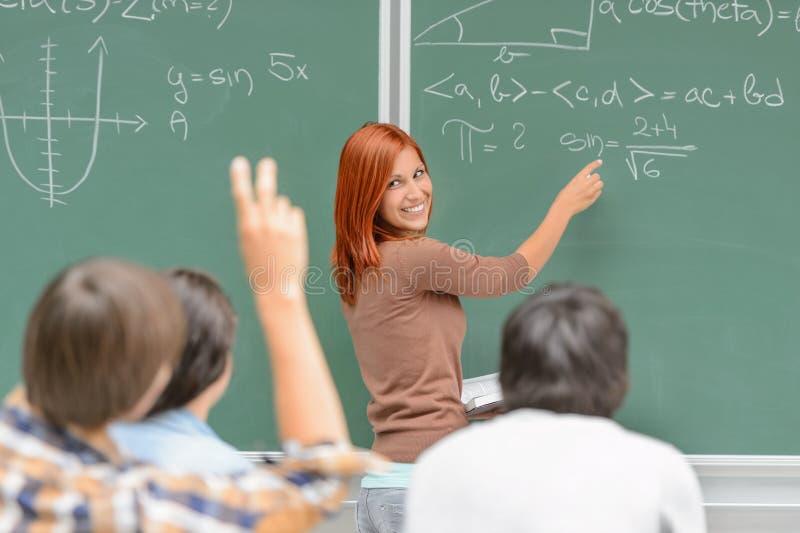Matematyka uczeń pisze na zielonych chalkboard kolega z klasy fotografia stock