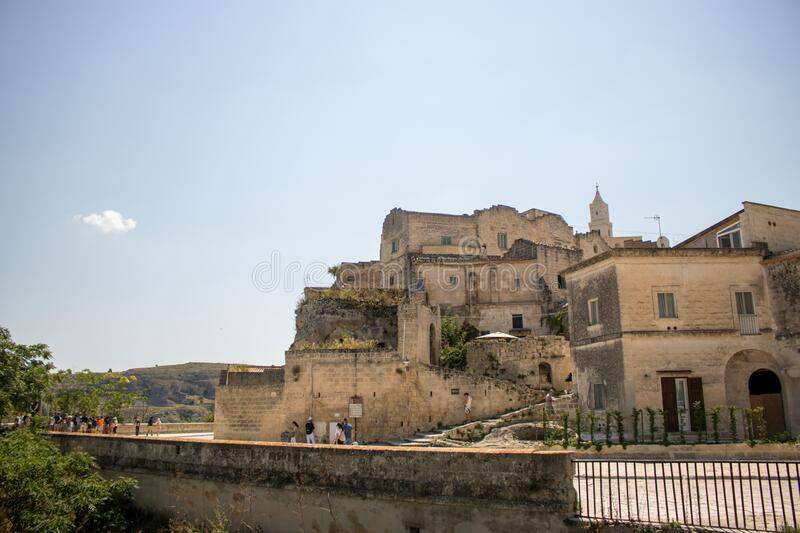 The city of Matera, Italy. Matera, Italy - August 10, 2020: the historic center of Matera and some tourists walking on the streets stock image