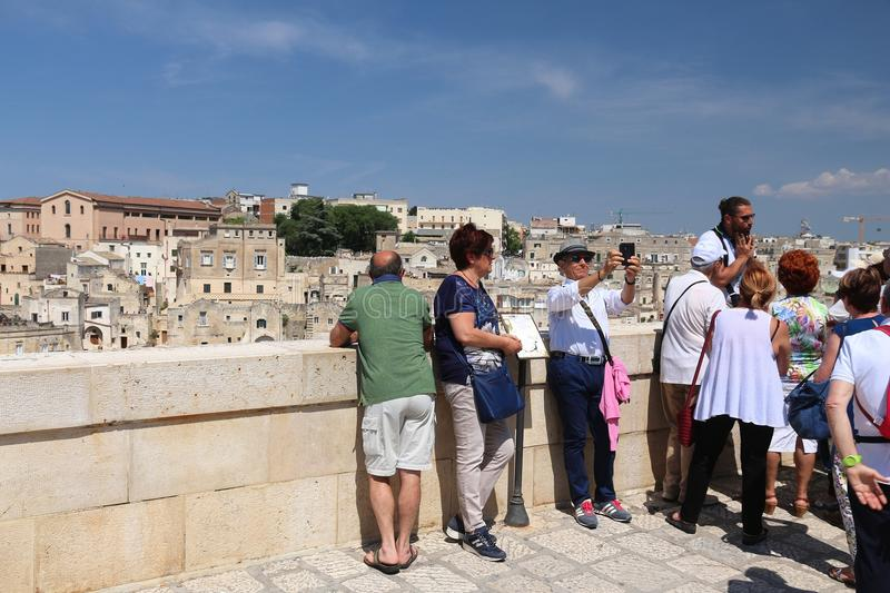 Matera tourists, Italy. MATERA, ITALY - JUNE 4, 2017: People visit Sassi districts overlook in Matera, Italy. The Old Town is listed as a UNESCO World Heritage royalty free stock photography