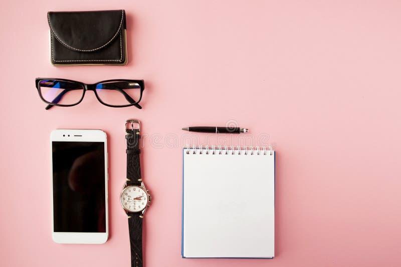 Materiały, biały smartphone, szkła, pióro, portfel, zegarek, kalendarz, notatnik R??owy t?o fotografia royalty free