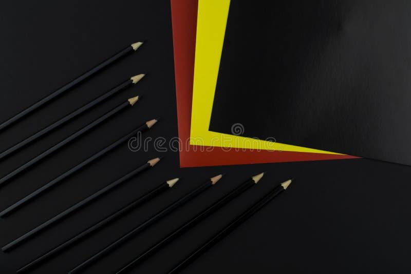 Materiały: czarni ołówki, barwiący papier są na czarnym tle zdjęcia royalty free
