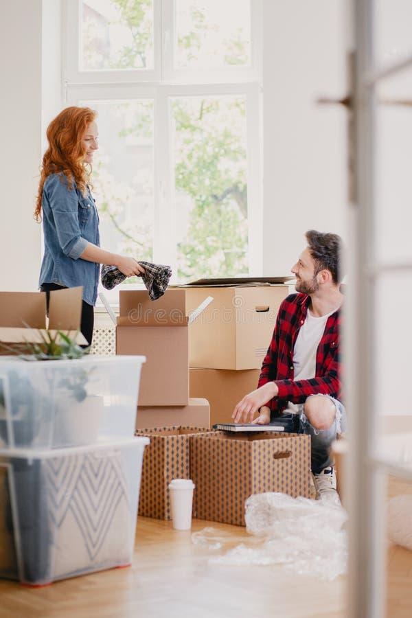 Materia del embalaje de la mujer y del hombre en las cajas del cartón mientras que mueve hacia fuera f imagen de archivo libre de regalías