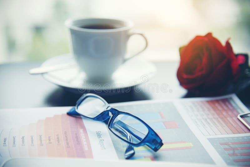 Materia del negocio, gráfico, cartas, calculadora, vidrios, pluma y una taza de café en la oficina la opinión de la ciudad es un  imagen de archivo