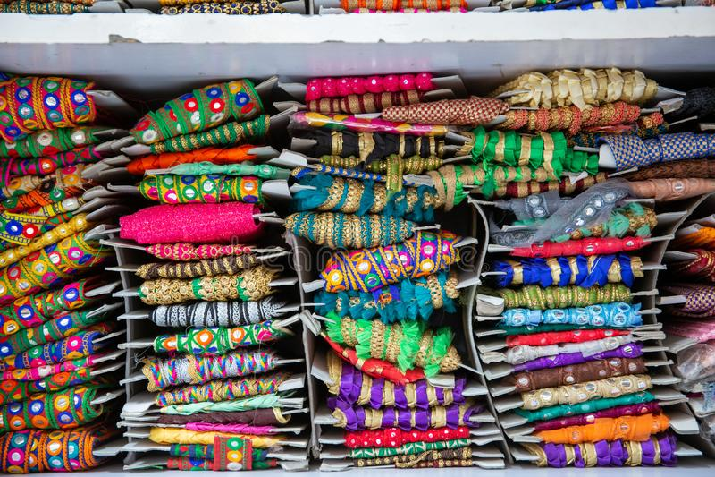 Materiais à medida coloridos como fitas e bordados em uma loja de rua no mercado de alfaiate em Mumbai, Índia imagem de stock